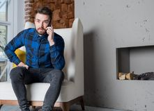 Man university student having cell telephone conversation. Male using device. Young stylish hipster guy calling via mobile phone, sitting in home interior near Stock Image