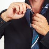 Man unleashes his tie over black shirt closeup Royalty Free Stock Photos