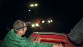 Man unload corn grain from the tractor trailer in silo. Night working. Loading grain into the bunker of a modern tractor for sowing. Winter crops. Agribusiness stock footage