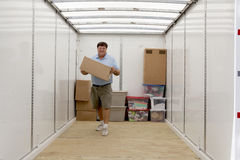 Man unloading portable storage unit. Man unpacking portable storage unit and caring boxes Royalty Free Stock Photo