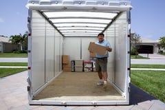 Man unloading portable storage unit. Man unpacking portable storage unit and caring boxes Stock Images
