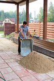 Man unloads sand from a wheelbarrow on track royalty free stock photos