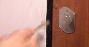 A man unlocks a house`s door with key and enters. stock video