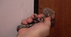 A man unlocks a house`s door with key and enters. stock footage