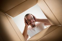 Free Man Unpacking And Opening Carton Box And Looking Inside Royalty Free Stock Photos - 123236828