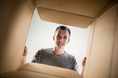 Free Man Unpacking And Opening Carton Box And Looking Inside Royalty Free Stock Image - 123237796