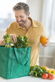 Man Unpacking Bag Of Groceries Royalty Free Stock Images