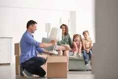 Man unpacking box while his family sitting on sofa indoors. Moving into new house royalty free stock photos