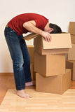 Man unpacking from cardboard boxes in a new home Stock Image
