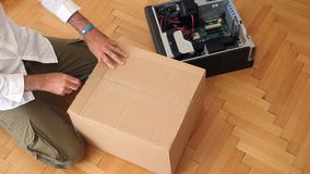 Man unpacking computer parts for upgrade of the Brocken computer. LONDON, UNITED KINGDOM - CIRCA 2017: Computer geek unboxing cardboard box with Documents stock video