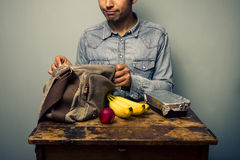 Man unpacking his lunch at old desk Royalty Free Stock Photos