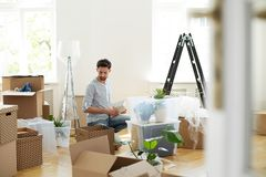 Man unpacking stuff from carton boxes after relocation to new home. Concept stock image