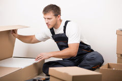 Man unpacking things after relocating Stock Images