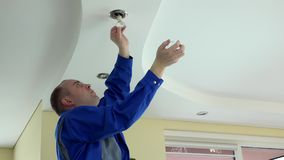 Man unscrew halogen bulb for replacing. Man in blue uniform unscrew halogen bulb for replacing stock video