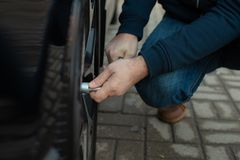 Man Unscrew the nuts  to remove wheel royalty free stock image