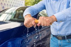 A man unscrews a rag, on a background a car. A man cleaning car with microfiber cloth. Man holds the microfiber in hand royalty free stock photo