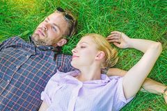 Man unshaven and girl lay on grass meadow. Closer to nature. Guy and girl happy carefree enjoy freshness of grass. Couple in love relaxing lay at meadow royalty free stock photo