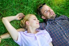 Man unshaven and girl lay on grass meadow. Closer to nature. Guy and girl happy carefree enjoy freshness of grass. Couple in love relaxing lay at meadow stock images