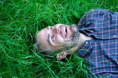 Man unshaven guy lay on green grass meadow. Guy happy and peaceful enjoy freshness of grass. Closer to nature. Man. Bearded hipster united with nature. Nature royalty free stock photos