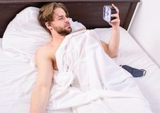 Man unshaven lay awake bed hold alarm clock. Man sleepy drowsy unshaven bearded face covered with blanket having rest. Stick sleep schedule same bedtime and stock image