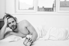 Man unshaven lay bed hold alarm clock. Man unshaven bearded wakeful face having rest. Stick schedule same bedtime wake royalty free stock photo