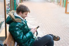Man unshaven wear warm jacket and hold smartphone snowy urban background. Guy sit bench interact smartphone. Communication concept. Hipster use smartphone on stock images