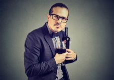Man unwilling to share with wine. Man in suit and glasses holding bottle and wineglass with feeling of ownership and looking at camera Royalty Free Stock Images