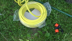 Man unwinding yellow watering hose stock footage