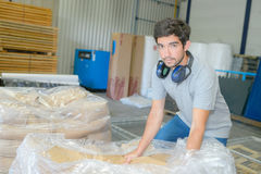 Man unwrapping plastic from pallet bags Stock Photos