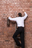 Man up against a brick wall Royalty Free Stock Image
