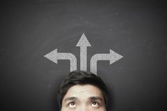 Man with up left and right arrows. On the blackboard background Royalty Free Stock Photography