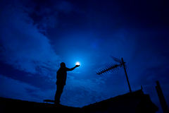 Man up on the roof,  holding full moon in hand against night sky Royalty Free Stock Image