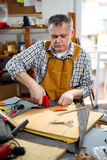 Man upholstering chair in his workshop Stock Image