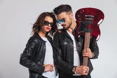 Man uppvisning av hans elektriska gitarr med kvinnan vid hans sida Royaltyfri Foto