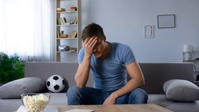 Man upset about defeat of football team, watching tv broadcast, unhappy fan. Stock photo royalty free stock photography