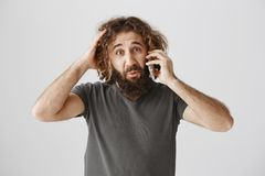 Man is upset friend canceled their meeting. Portrait of gloomy frustrated eastern guy with beard and curly hair. Scratching head and expressing sadness while Royalty Free Stock Photo
