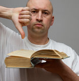 Man upset read a book show thumbs down  on gray background Stock Image