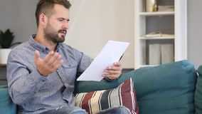 Man Upset after Reading Documents, Feeling Sad. High quality stock images