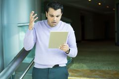 Man upset by what he sees on tablet royalty free stock photo