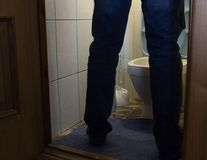A man urinates in the toilet, men`s legs, health problems, prostatitis and adenoma. Restroom stock photography