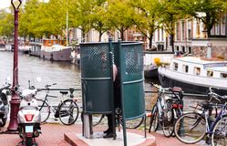 Man urinating in Amsterdam in a public urinal. Facility stock images