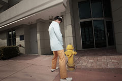 Man urinating on a fire hydrant Stock Image