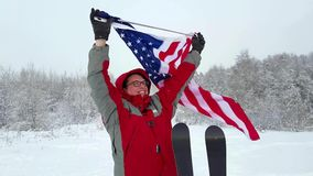Man with US flag on a ski slope. Happy positive caucasian Man waving a flag of the United States of America winter time on a ski slope stock video footage