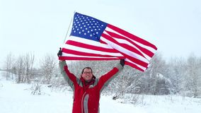 Man with US flag on a ski slope. Happy positive caucasian Man waving a flag of the United States of America winter time on a ski slope stock video