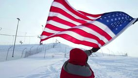 Man with US flag on a ski slope. Happy positive caucasian Man waving a flag of the United States of America winter time on a ski slope. Back view stock footage