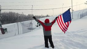 Man with US flag on a ski slope. Man waving a flag of the united states in winter on a ski slope stock video footage