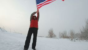 Man with US flag on a ski slope. Man waving a flag of the United States in winter on a ski slope stock footage