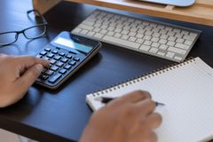 man use calculator make note with calculate about cost in offi royalty free stock photo