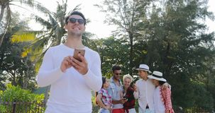 Man Use Cell Smart Phone Chatting Online Over Young People Group In Tropical Palm Tree Park. Slow Motion 60 stock video