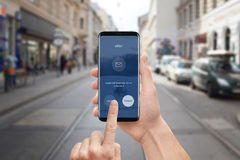 Man use email app on mobile phone. Modern smart phone with round edges and flat user interface design. Street in background royalty free stock images